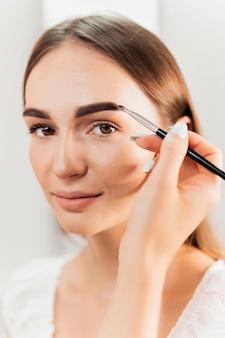 Make-up master robi makijaż dla klienta patrzącego w kamerę. malowanie brwi
