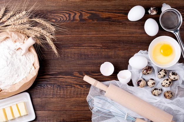 Mąkę w papierowej torebce, jajkach, maśle, wałku i trzepaczce do pieczenia