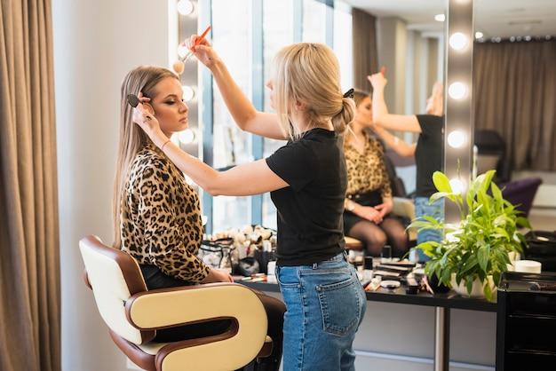 Makeup artysta stosuje proszek na kobiety twarzy