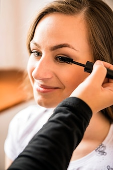 Makeup artysta stosuje tusz do rzęs na szczęśliwej kobiety twarzy
