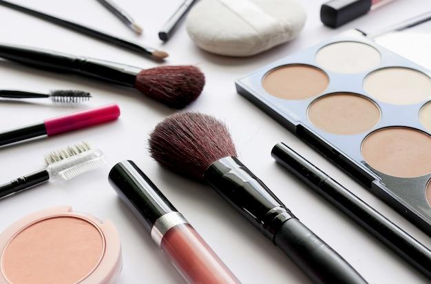 Makeup kosmetyki na bielu stole z nadmiernym światłem i miękką ostrością w tle