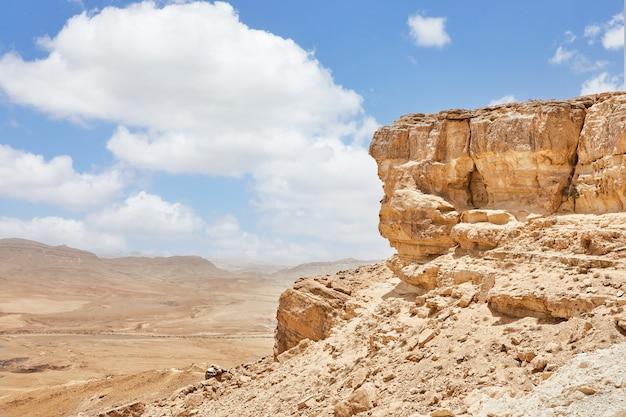 Makhtesh ramon - krater ramon na izraelskiej pustyni negev z punktu widokowego micpe ramon, z górą ramon w tle. widok kolorowy piasek, kamienna pustynia negev w dół od urwiska.