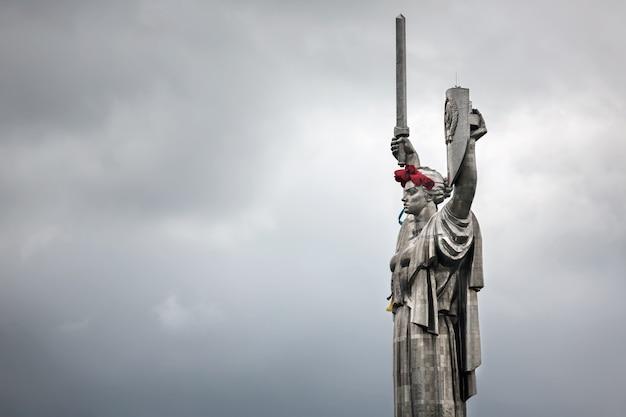 Maki pamięci. pomnik matki ojczyzny udekorowany wieńcem maków w dniu pamięci i pojednania w kijowie na ukrainie