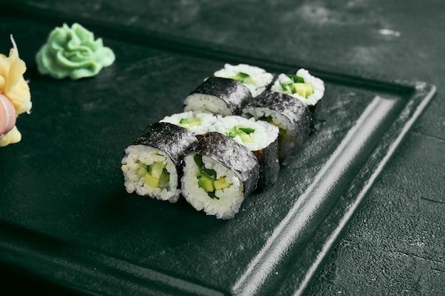 Maki sushi roll z awokado. klasyczna kuchnia japońska. dostawa jedzenia. czarne tło