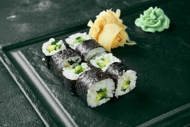 Maki sushi roll z ogórkiem. klasyczna kuchnia japońska. dostawa jedzenia. czarne tło