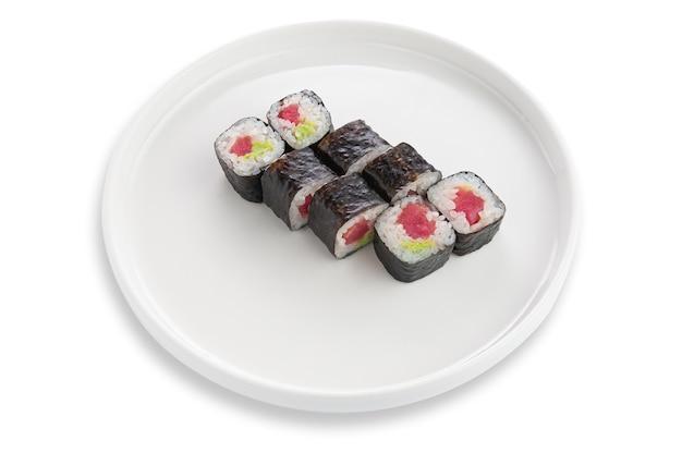 Maki sushi roll z tuńczykiem i wasabi. na białym talerzu ceramicznym. białe tło. odosobniony.