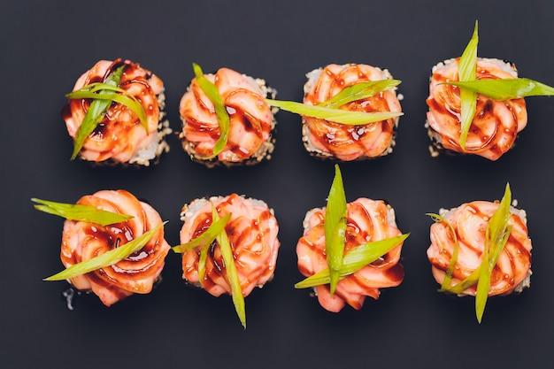 Maki sushi rolls z łososiem na czarnym kamieniu na ciemnym tle. z imbirem i wasabi. menu sushi. japońskie jedzenie. zbliżenie na pyszne japońskie jedzenie z rolką sushi. poziome zdjęcie.