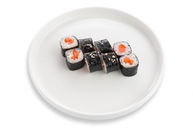 Maki sushi z łososiem i sezamem. na białym talerzu ceramicznym. białe tło. odosobniony.