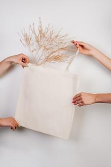 Makieta bawełniana ręcznie robiona eko torba na zakupy w ręku biała torba wykonana z materiałów pochodzących z recyklingu na białym tle...