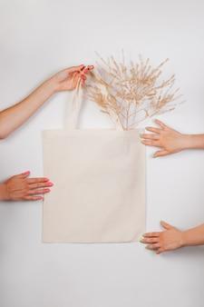 Makieta bawełniana ręcznie robiona eko torba na zakupy w ręku biała torebka wykonana na białym tle z...