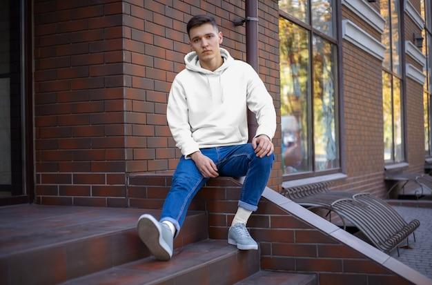 Makieta biała bluza z kapturem na młodym mężczyźnie przy ścianie z cegły. przedni widok. projekt mody do prezentacji w sklepie. szablon codziennych ubrań