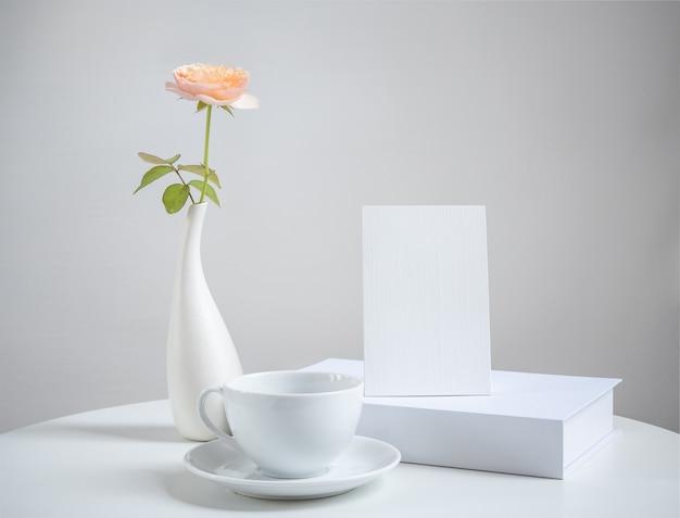 Makieta biała filiżanka kawy z zaproszeniem i piękne pomarańczowe kwiaty róży w nowoczesnym wazonie ustawionym na białym drewnianym stole