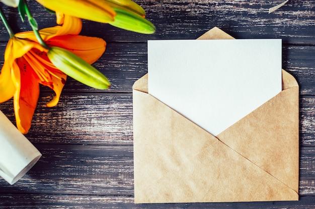 Makieta biała kartka z pozdrowieniami i rzemiosło koperta z leluj kwiatami na drewnianym tle