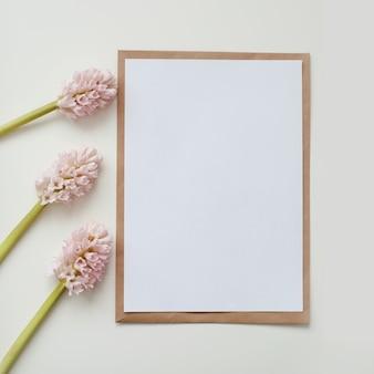 Makieta biała kartka z życzeniami i koperta z kwiatami na tle