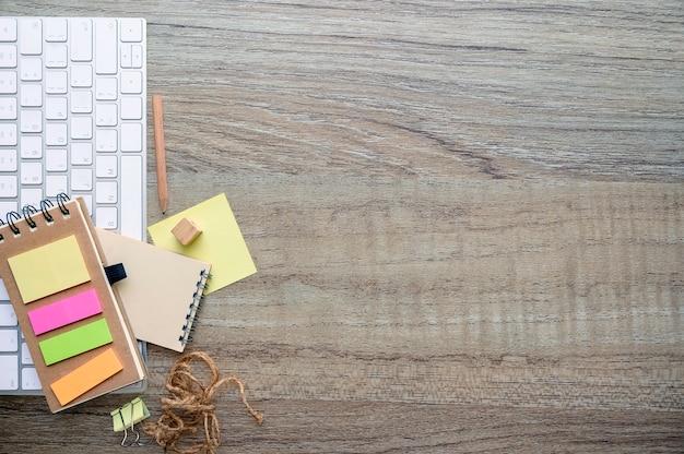 Makieta biała klawiatura z materiałami na drewnianym blacie.