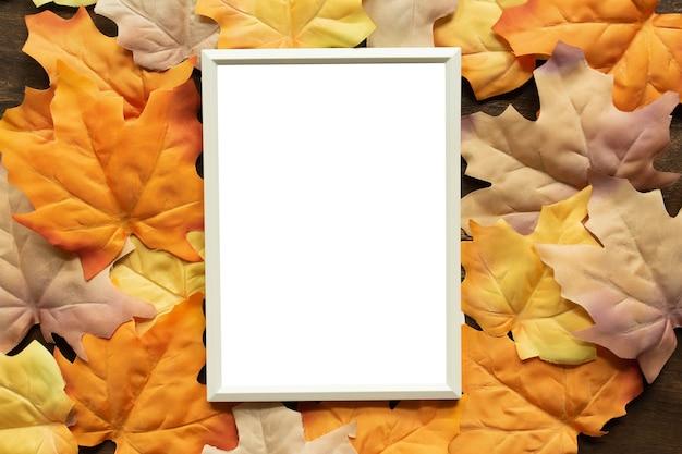 Makieta biała pusta papierowa ramka z grupą suszonych pomarańczowych liści klonu w tle