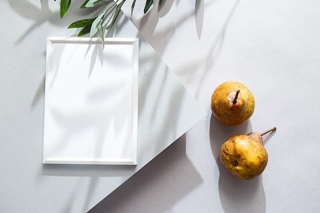 Makieta biała ramka na zdjęcia letnia kompozycja z gruszkami i cieniem gałązki oliwnej