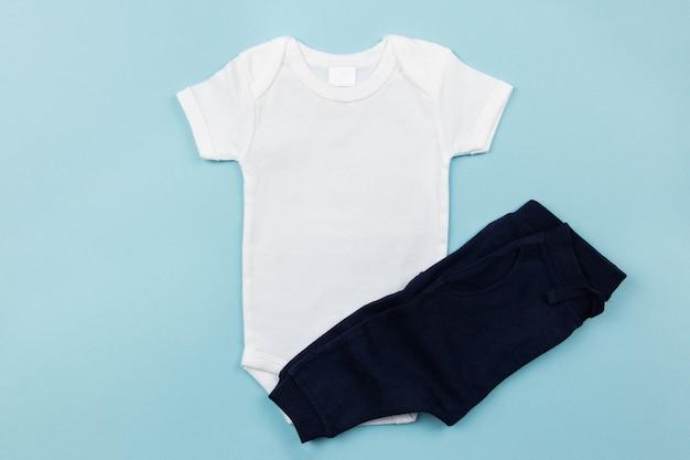 Makieta białego body dla chłopca leżała płasko z ciemnymi majtkami na niebieskiej powierzchni