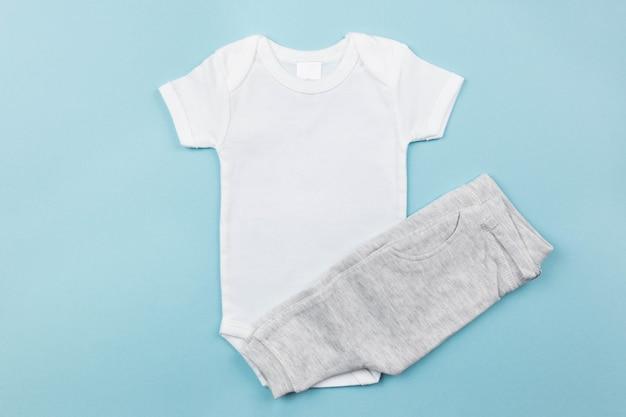 Makieta białego body dla chłopca leżała płasko z szarymi majtkami na niebieskiej powierzchni