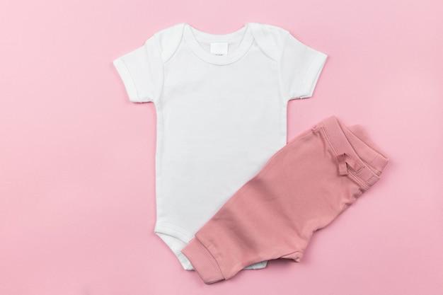 Makieta białego body dla dziewczynki leżącej płasko z majteczkami na różowej powierzchni