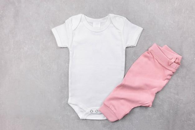 Makieta białego body dla dziewczynki leżącej płasko z różowymi majtkami na szarej betonowej powierzchni