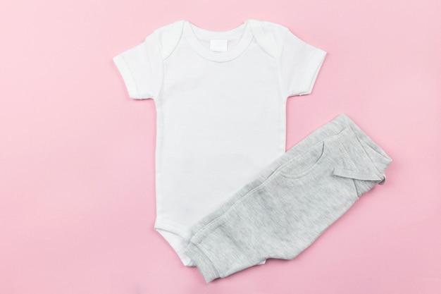 Makieta białego body dla dziewczynki leżącej płasko z szarymi majtkami na różowej powierzchni