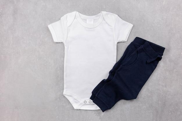 Makieta białego body niemowlęcego leżała płasko z ciemnoniebieskimi majtkami na szarej betonowej powierzchni