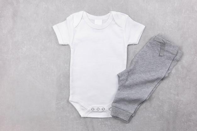 Makieta białego body niemowlęcego leżała płasko z szarymi majtkami na betonowej powierzchni