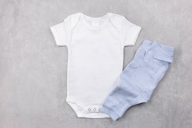 Makieta białego body niemowlęcego płasko leżała z niebieskimi majtkami na szarej betonowej powierzchni