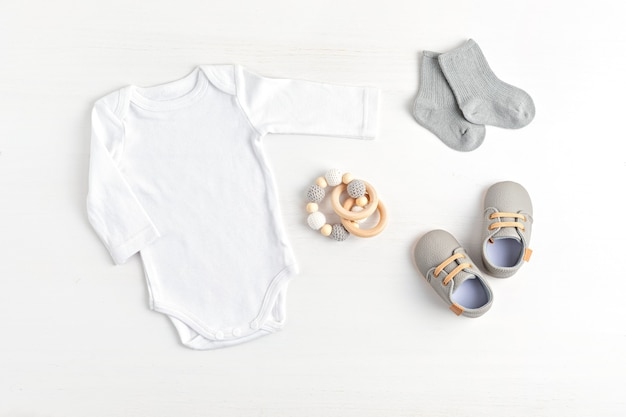 Makieta białego body niemowlęcego wykonanego z bawełny organicznej z ekologicznymi akcesoriami niemowlęcymi. szablon onesie dla marki, logo, reklamy. płaski układanie, widok z góry