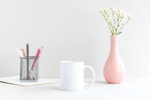 Makieta białego kubka z papeterią, różowym wazonem i gałązką gipsówki na stole