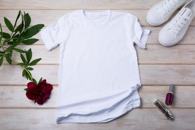 Makieta białej bawełnianej koszulki damskiej z butami sportowymi, bordową piwonią, lakierem do paznokci i szminką. zaprojektuj szablon koszulki, makieta prezentacji nadruku koszulki