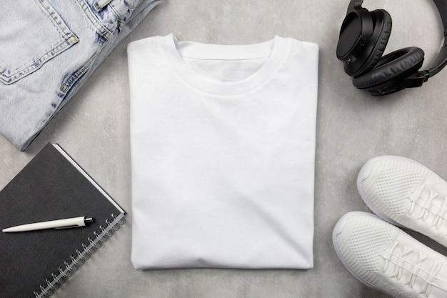 Makieta białej bawełnianej koszulki damskiej z dżinsami i trampkami, notatnikiem i czarnymi słuchawkami. zaprojektuj szablon koszulki, wydrukuj makietę prezentacji.