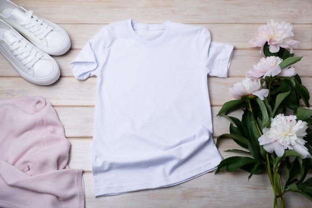 Makieta białej bawełnianej koszulki damskiej z różowym swetrem, sportowymi butami i delikatnymi piwoniami. zaprojektuj szablon koszulki, makieta prezentacji nadruku koszulki