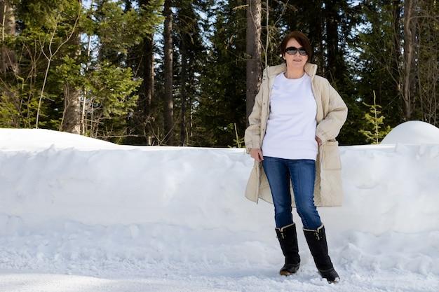 Makieta białej bluzy polarowej z okrągłym dekoltem przedstawiająca kobietę w beżowym pikowanym płaszczu i czarnych śniegowcach. szablon bluza o dużej gramaturze