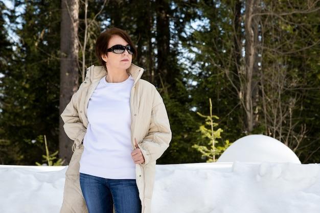 Makieta białej bluzy polarowej z okrągłym dekoltem przedstawiająca kobietę w beżowym pikowanym płaszczu w zaśnieżonym lesie. szablon bluza o dużej gramaturze