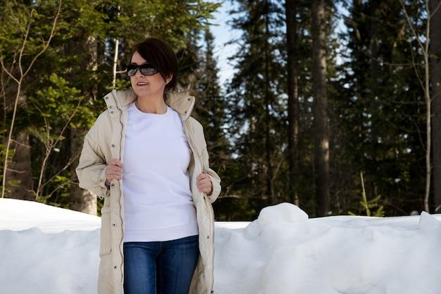 Makieta białej bluzy polarowej z okrągłym dekoltem przedstawiająca kobietę z asymetryczną fryzurą w zimowym drewnie. szablon bluza o dużej gramaturze