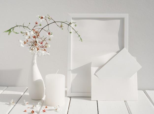 Makieta białej karty z zaproszeniem, ramka plakatu, świeca i piękne kiwające się kwiaty clerodendron w ceramicznym wazonie na drewnianym stole w białym pokoju, karta z pozdrowieniami w delikatnym tonie martwa natura
