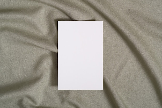 Makieta białej pustej karty papieru na zielonej neutralnej kolorowej tkaninie