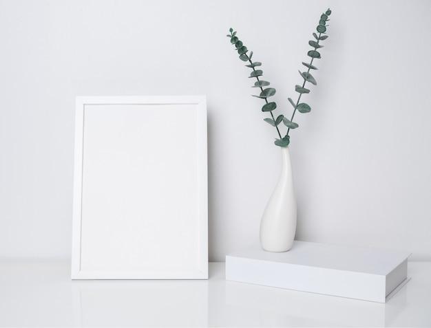 Makieta białej ramki plakatowej i książki z liśćmi eukaliptusa w nowoczesnym ceramicznym wazonie na białym stole