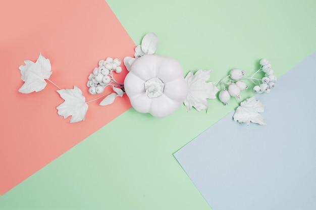 Makieta białej ramki z dynią, jagodami i liśćmi na wielokolorowym pastelowym tle jesień. kartka z życzeniami.