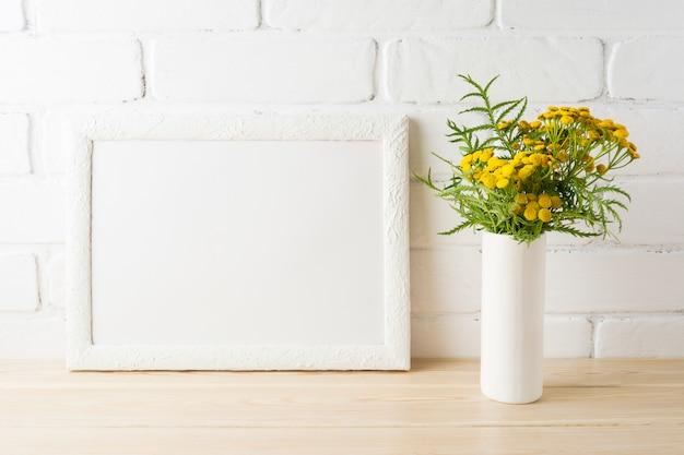 Makieta białej ramki z żółtymi kwiatami w pobliżu pomalowanych ścian z cegły