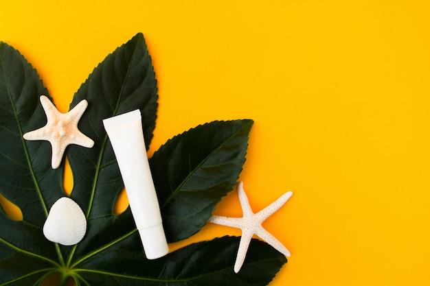 Makieta białej tuby z gwiazdą morską na zielonym liściu na żółtym tle