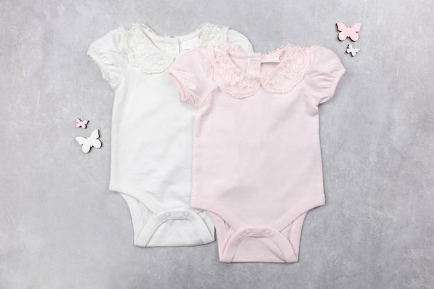 Makieta biało-różowego body dla dziewczynki leżała płasko na szarej betonowej powierzchni