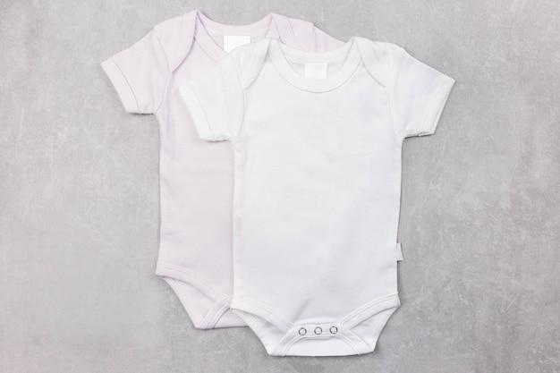 Makieta biało-różowych body niemowlęcych na szarej betonowej powierzchni