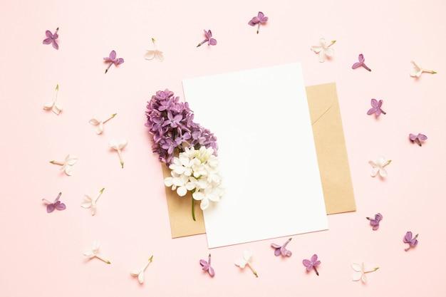 Makieta biały kartkę z życzeniami i koperty z gałęzi bzu na jasnym tle