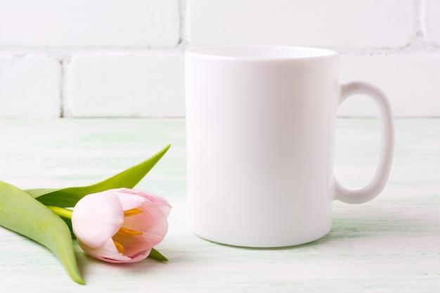 Makieta biały kubek kawy z różowym tulipanem
