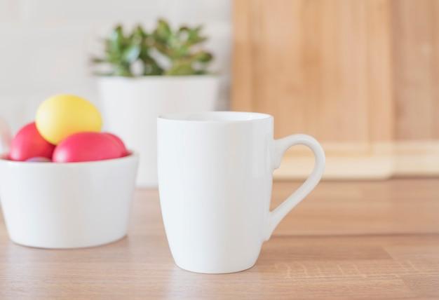 Makieta biały kubek - motyw wielkanocny. pisanki. kolorowe jajka w kolorze czerwonym i żółtym, z bliska. przybory kuchenne w nowoczesnym wnętrzu kuchni