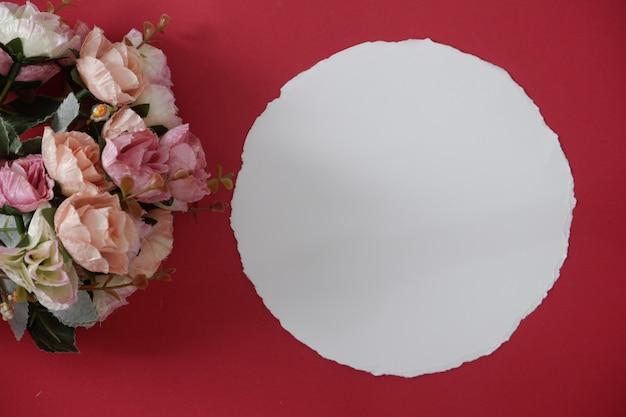 Makieta biały papier z przestrzenią dla teksta lub obrazka na czerwonym tle i kwiacie.
