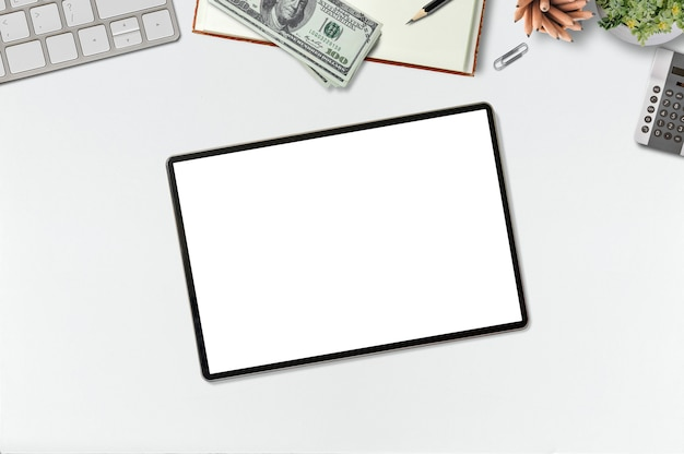 Makieta biurka z pustym ekranem tabletu, laptopa, pieniędzy i materiałów eksploatacyjnych.